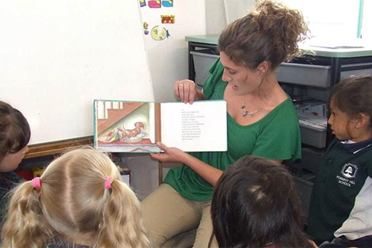 Teacher reading to a group of students as part of the Global Gateway program.