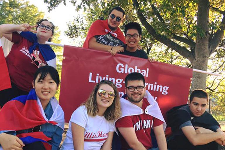 Students wearing flags in front of a sign for the Global Living Learning Center at IU Bloomington.