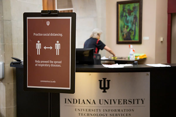 A maintenance worker disinfects a desk behind sign encouraging people to practice social distancing at the IMU.