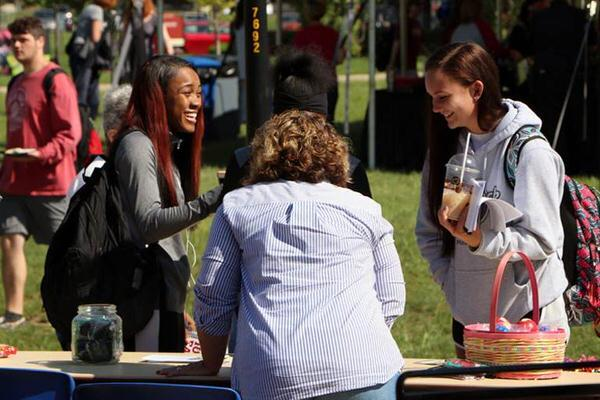 Two female students talking at an outdoor student club fair on the IU East campus.