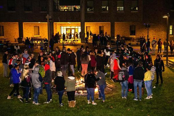 Large group of students in front of bonfire on the IU East campus.