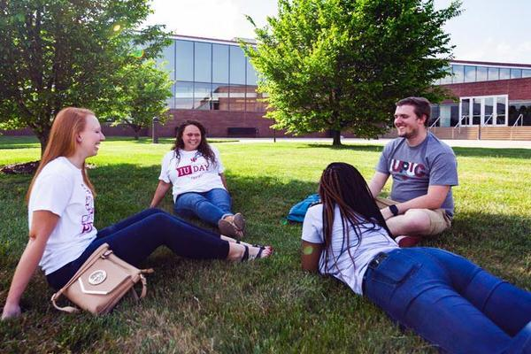 Four students sitting outside in the grass on IUPUC campus.