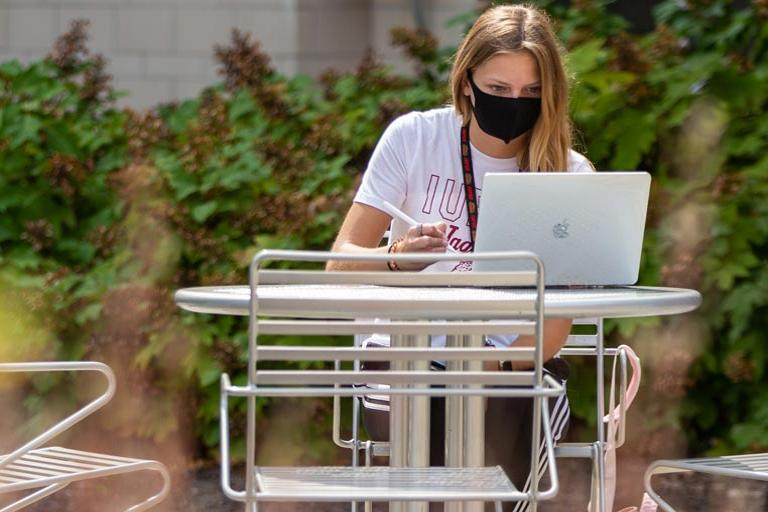 Female IUPUI student studying outside.