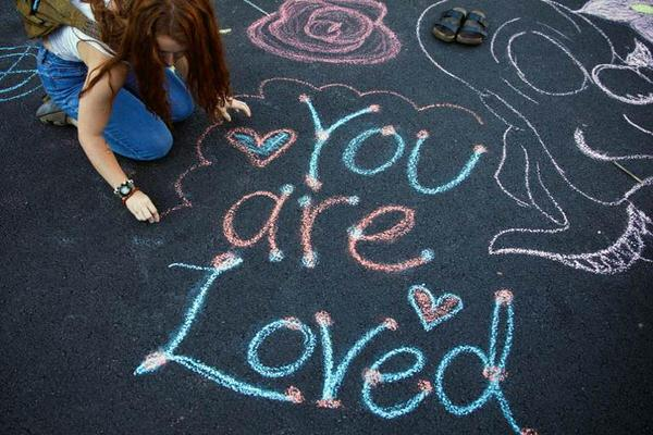 You are loved written on the ground in chalk.